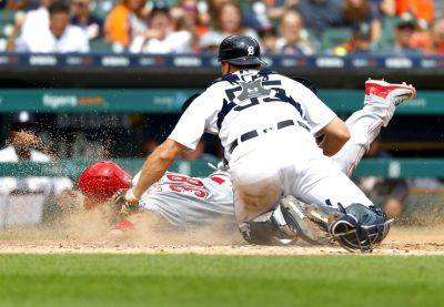 Detroit Tigers catcher John Hicks (55) tags out Cincinnati Reds' Curt Casali at home plate in the seventh inning of Wednesday's game in Detroit. (AP photo)