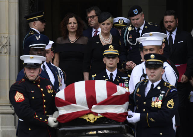 The casket of Sen. John McCain, R-Ariz., is carried out of the Washington National Cathedral in Washington, Saturday after a memorial service, as Cindy McCain is escorted by her son Jimmy McCain and other family members.