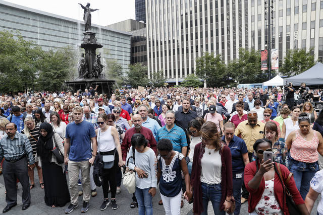 Mourners hold hands during a vigil Friday, Sept. 7, 2018 in Cincinnati's Fountain Square near the site of Thursday's fatal shooting. Suspect Omar Enrique Santa Perez was killed by police officers. (AP Photo/John Minchillo)