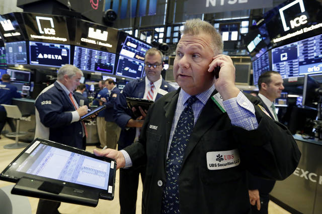 FILE- In this Aug. 27, 2018, file photo trader George Ettinger, foreground, works on the floor of the New York Stock Exchange. The U.S. stock market opens at 9:30 a.m. EDT on Monday, Sept. 10. (AP Photo/Richard Drew, File)