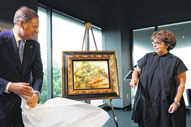 "U.S. attorney Geoffrey Berman, left, unveils a Renoir painting with Sylvie Sulitzer at a news conference Wednesday in New York. The 1919 oil painting ""Femmes Dans Un Jardin"" was seized in Paris by the Nazis from Sulitzer's grandfather. It was returned to Sulitzer, a delicatessen owner from the south of France, in the ceremony."