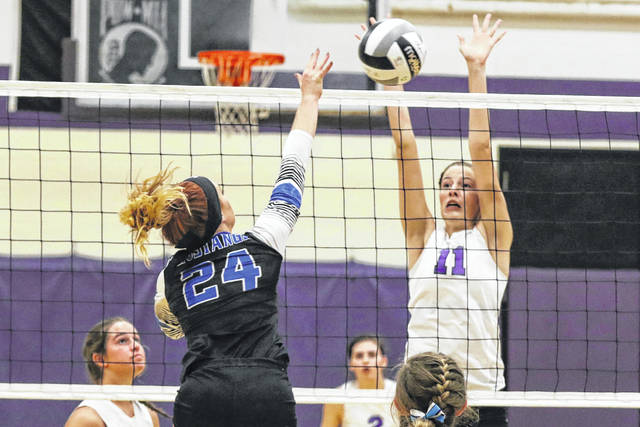 Ada's Megan Light goes up to defend a shot by Allen East's Maddie Henry during Thursday night's Northwest Conference match at Ada.