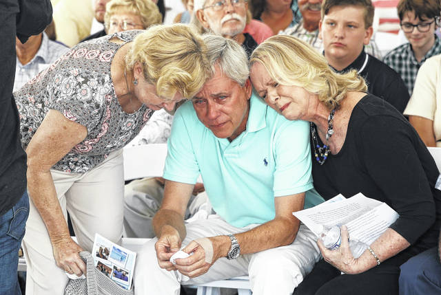 Carl Hiaasen, center, brother of Rob Hiaasen, one of the journalists killed in the shooting at The Capital Gazette newspaper offices, is consoled by his sisters Barb, left, and Judy during a memorial service in Owings Mills, Md., on July 2. (AP Photo/Patrick Semansky)
