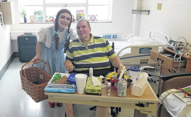 "Sydney Hartford, dressed as Dorthy Gale in ""The Wizard of Oz,"" visits William Cooley a patient at Mercy Health-St. Rita's Medical Center, Monday."