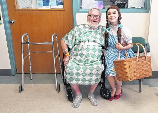 "Sydney Hartford, dressed as Dorthy Gale in ""The Wizard of Oz,"" visits Pat Bolling a patient at Mercy Health-St. Rita's Medical Center, Monday."