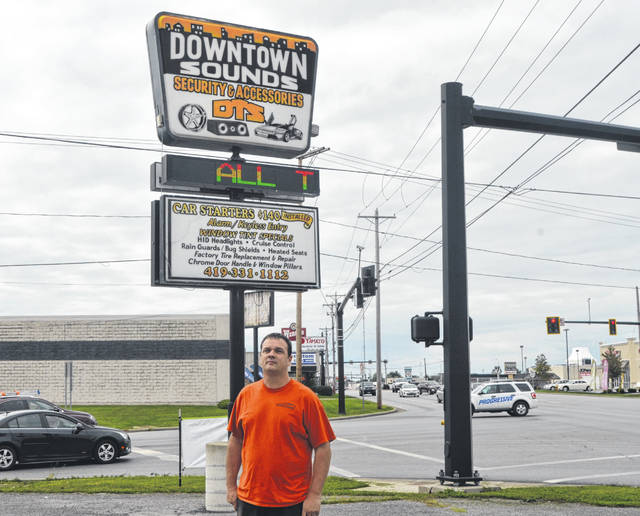 John Poling, owner of Downtown Sounds on 2193 Elida Road, stands outside by the store's sign.