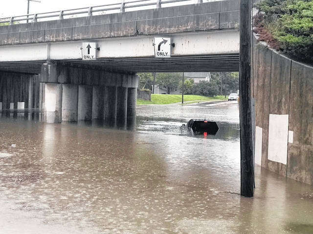 A nearly submerged vehicle has been abandoned with lights still on at the St. Johns underpass in Lima. Heavy rains impacted the region Thursday evening with flooding in low-lying areas. Auglaize County Sheriff's Office also issued an alert.