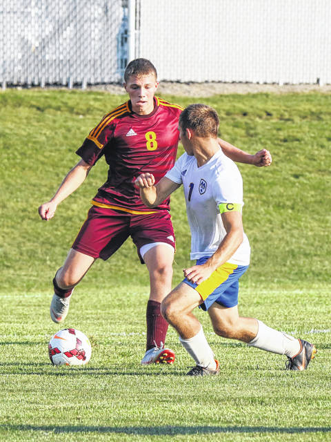Kalida's Gabe Hovest looks to make a pass being defended by St. Marys' Howie Spencer during Tuesday night's match at Kalida. See more match photos at LimaScores.com.