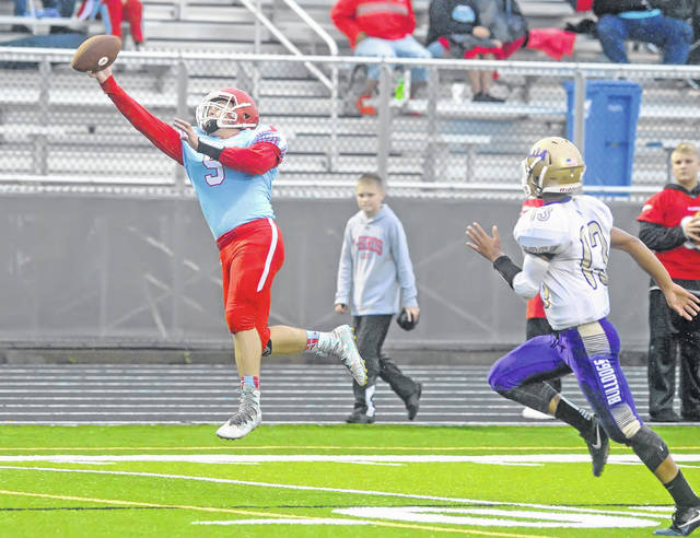 Lima Central Catholic's Michael Jay Riepenhoff catches a pass ahead of Ada's Daniel Mattson during Saturday night's game at Spartan Stadium.