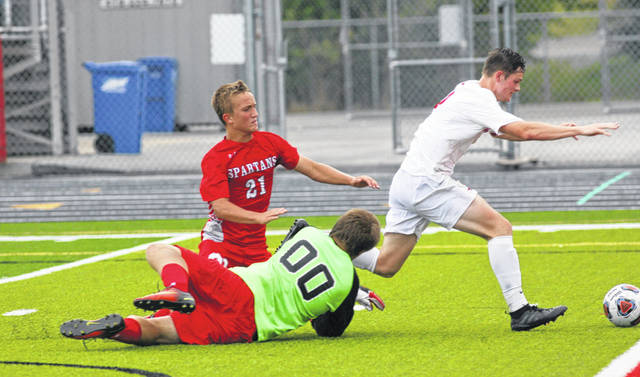 Lima Central Catholic's Trey Horstman splits Lima Senior defender Aaron Bowsher and goalie Ryan Utendorf to collect his third goal of Saturday's game at Spartan Stadium.
