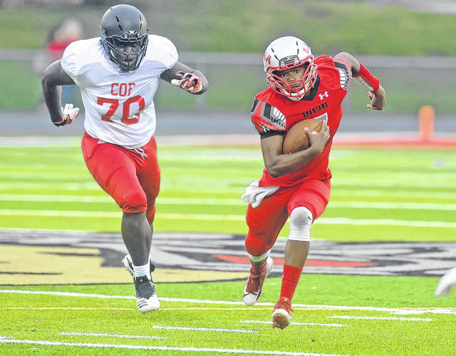 Lima Senior's Rashad Wallace scrambles for yards ahead of COF Academy's Oussaine Gai during Friday night's game at Spartan Stadium. Wallace rushed for 127 yards on 14 carries and a fourth-quarter touchdown.