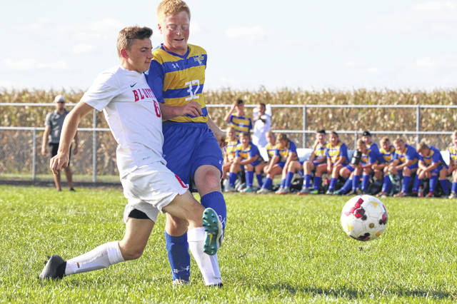 Lincolnview's Aaron Cavinder (32) attempts to clear the ball against Bluffton's Tayton Kleman during Tuesday night's match at Lincolnview.gets a touch on it for a goal on Tuesday evening.
