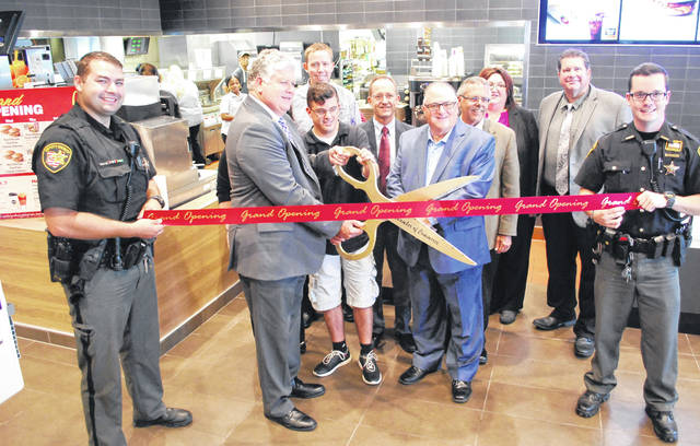 A ribbon cutting ceremony was held Friday at McDonald's, located at 1965 N. West St. in Lima. From left: Allen County Sheriff deputy Jared Gesler, holding ribbon; Lima/Allen County Chamber president Jed Metzger; Jon Tenwalde; McDonald's owner Jerry Lewis; and Allen County Sheriff deputy Logan Curfman, holding ribbon. Back row: McDonald's marketing director Ryan Lowry; McDonald's director of operations Scott Shaw; McDonald's director of training Dave Stover; Jennu Sumption, general manager of the North West Street location; and Tom Simon, supervisor at the restaurant.
