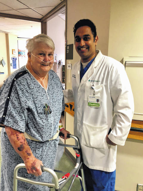 Mercy Health-St.Rita's interventional cardiologist Dr. Sandeep Patel walks with patient Lois Edgington after her minimally invasive transcatheter aortic valve replacement surgery Tuesday at Mercy Health-St. Rita's Medical Center.