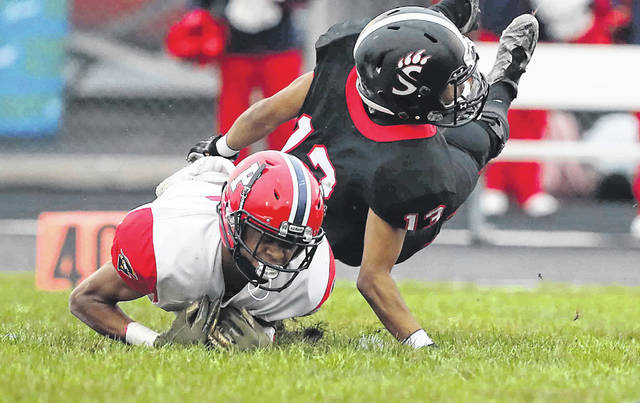 Perry's Chazz Jackson goes low to make a reception against Spencerville's Drew Armstead during Friday night's game at Spencerville
