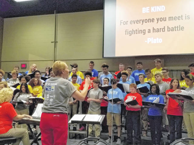 Lima Senior choir director Amy Phillips directs a choir of students from Lima Senior, Shawnee and Spencerville schools at the United Way Day of Caring kickoff Friday at Veterans Memorial Civic Center in downtown Lima.