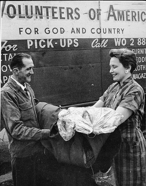 A patron drops off clothing to The Volunteers of America in 1959. The people are unidentified. The group provided odd jobs for men in need of work.
