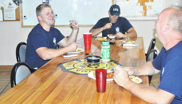 Lima Fire Department firefighters Lucas Hastings, Erick Hayes and Lt. Andrew Groman eat Italian food delivered to Central Fire Station by the Olive Garden restaurant in Lima.