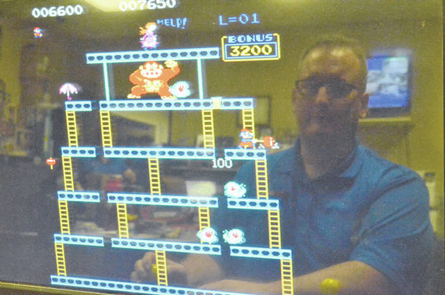 """Barry Electronics Sales Manager Jeff Smith, 41, of Elida, plays """"Donkey Kong"""" on a arcade system in his store."""