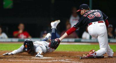 Detroit's JaCoby Jones scores past the Indians' Neil Ramirez after a wild pitch by Ramirez during the eighth inning of Friday night's game in Cleveland. (AP photo)
