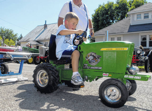 A youngster competes in a kiddie tractor pull.