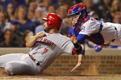 Cincinnati Reds' Eugenio Suarez is tagged out at home plate by the Cubs' Victor Caratini during Friday night's game in Chicago. (AP photo)