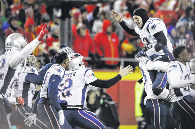 New England Patriots quarterback Tom Brady (12) celebrates with his  teammates after the AFC aa5830280